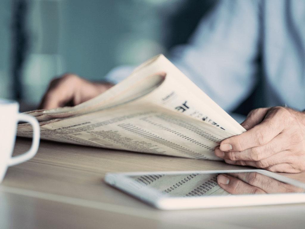 clovek ktory v ruke drzi noviny